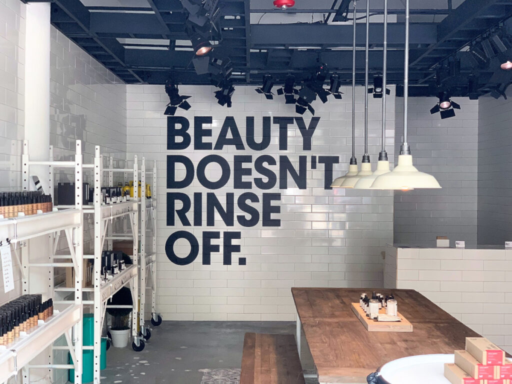 """Eine Wand mit """"Beauty Doesn't Rinse Off"""" Text"""